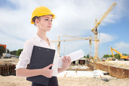 executive helmet: business woman architect in yellow builder helmet at construction site Stock Photo