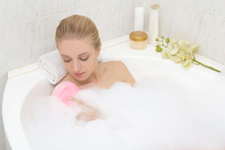 woman bathing: young attractive slim woman bathing with pink sponge
