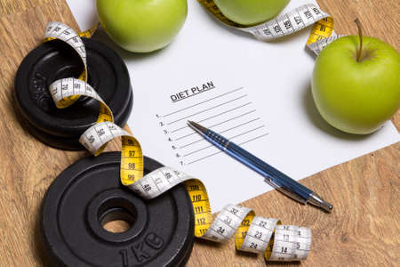 weightloss plan: sheet of paper with diet plan, apples and dumbbell on wooden background