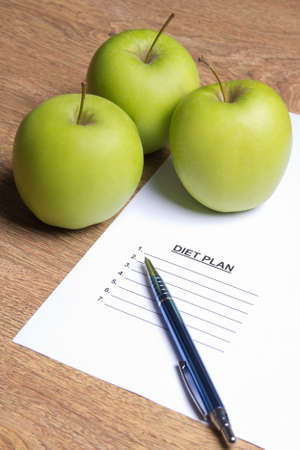diet plan: sheet of paper with diet plan, pen and green apples