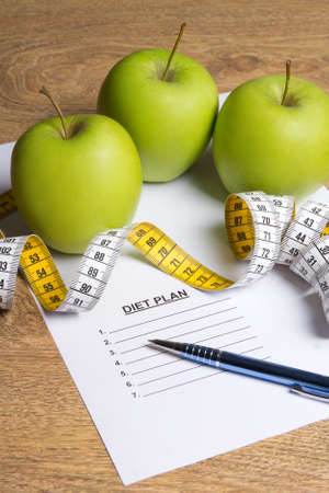 weightloss plan: diet concept - paper with diet plan, green apples and measure tape on wooden table