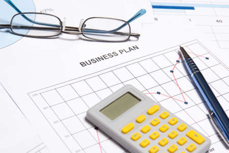business plan concept - graphs, charts, pen, and calculator on the table photo