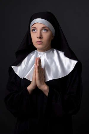 religious habit: religion concept - young praying nun over grey background Stock Photo