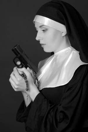 black nun: black and white portrait of young woman nun holding gun