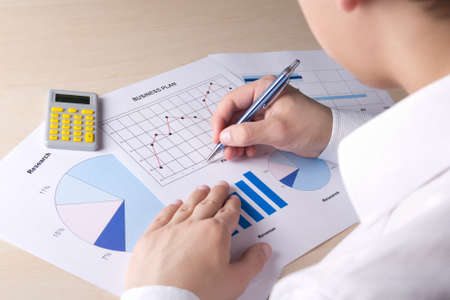 bussinessman: business concept - bussinessman accounting something with calculator in office