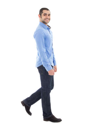 side view of young arabic bearded business man in blue shirt walking isolated on white background photo