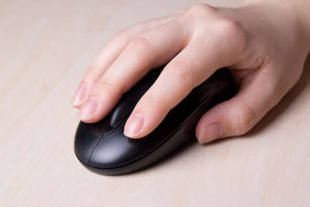 wireless mouse in female hand on table photo