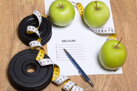 diet plan concept - green apples, measure tape and dumbbell photo