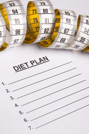 weightloss plan: close up of measure tape on paper with diet plan Stock Photo