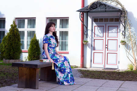 young beautiful woman in dress sitting on the bench in old town of Tallinn, Estonia photo