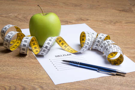 paper with diet plan, apple and measure tape on wooden table