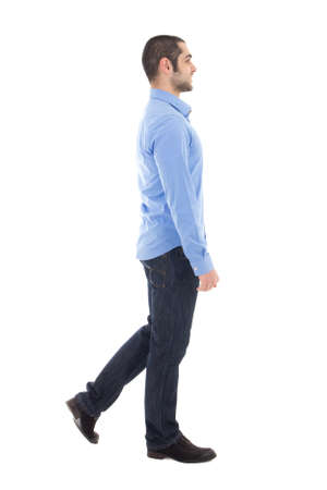 side view of young arabic business man in blue shirt walking isolated on white background