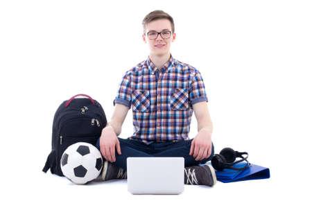 niño con mochila: Adolescente hermoso que se sienta con el portátil, mochila y balón de fútbol aislado en el fondo blanco Foto de archivo