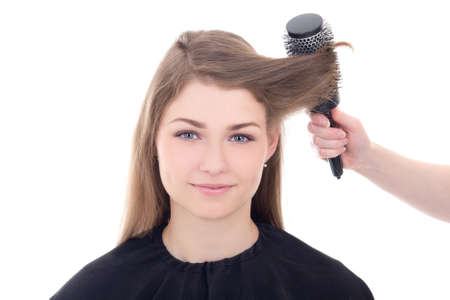 hairdresser doing haircut to young beautiful woman isolated on white background photo