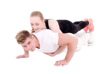 workout and love concept - young muscular man doing push ups with beautiful woman on back isolated on white background photo