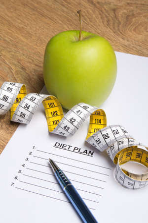 weightloss plan: close up of paper with diet plan, pen, apple and yellow measure tape on wooden table Stock Photo