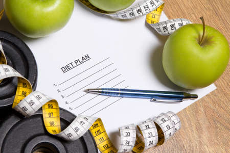 sheet of paper with diet plan, apples, dumbbell and measure tape