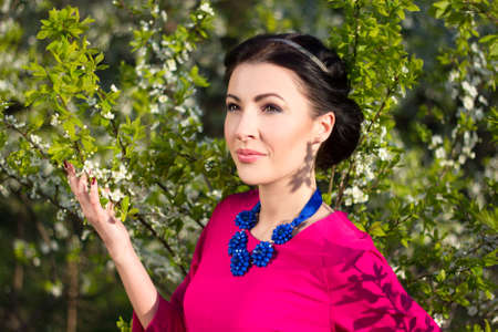 cherrytree: young beautiful woman posing in cherry-tree garden