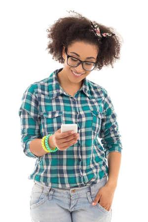 afroamericanas: concepto sms - bella adolescente afroamericano con el teléfono móvil aislado en el fondo blanco