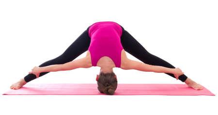 slim woman doing stretching exercise on yoga mat isolated on white background photo
