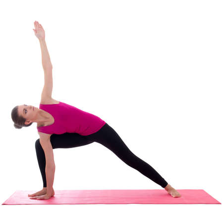revolved: beautiful slim sporty woman standing on pink mat in yoga pose isolated on white background