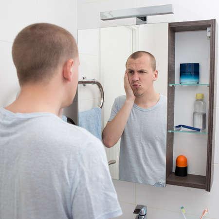 sleepy man: hangover concept - tired or sleepy man looking at mirror in bathroom
