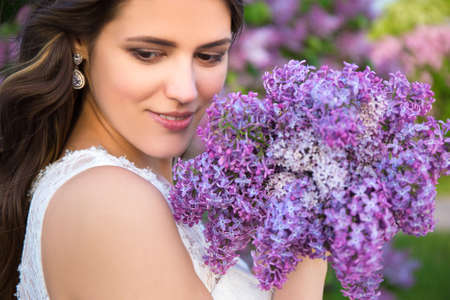 close up portrait of happy beautiful bride with big bouquet of lilac flowers photo