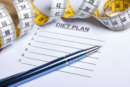 weightloss plan: paper with diet plan, pen and yellow measure tape