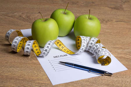 weightloss plan: close up of paper with diet plan, green apples and measure tape on wooden table