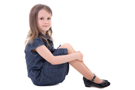sit studio: cute little girl in denim dress sitting isolated on white background