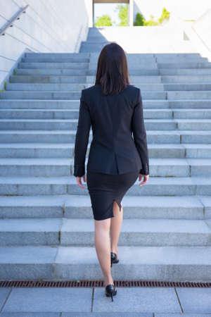 faldas: concepto de carrera - vista trasera de joven mujer de negocios en las escaleras