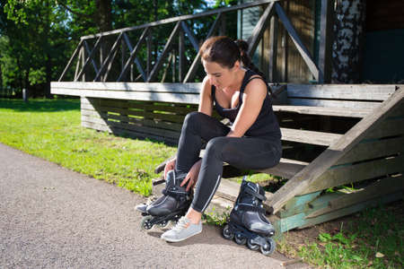 blading: young slim woman sitting and putting on skates in park Stock Photo