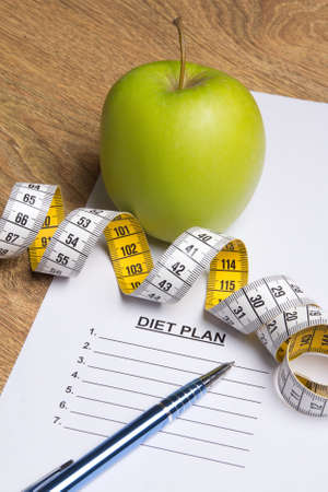 close up of paper with diet plan, pen, green apple and measure tape Stock Photo