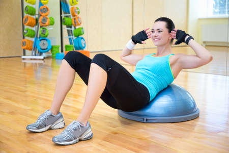 personal trainer: woman doing exercises for abdominal muscles on bosu ball in gym