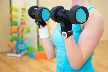 Mujer deportiva que ejercita con pesas en el gimnasio