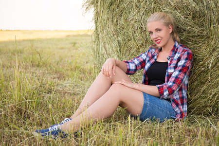 haystacks: young beautiful blonde woman sitting in field with haystacks