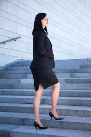 suit skirt: success concept - young beautiful business woman standing on stairs