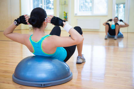 abs: young woman doing exercises on bosu ball in gym