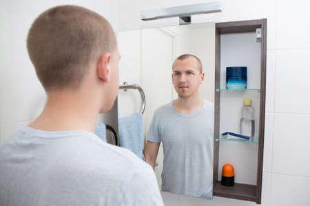cuarto de baño: apuesto hombre que mira el espejo en el baño