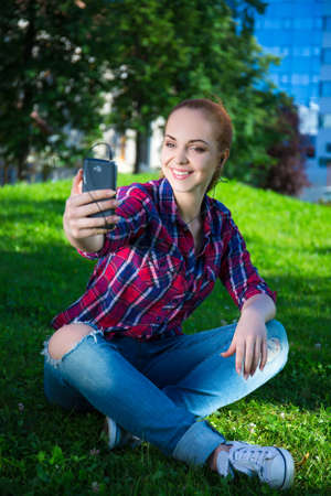 making music: teenage girl listening music and making selfie photo with smart phone in summer park