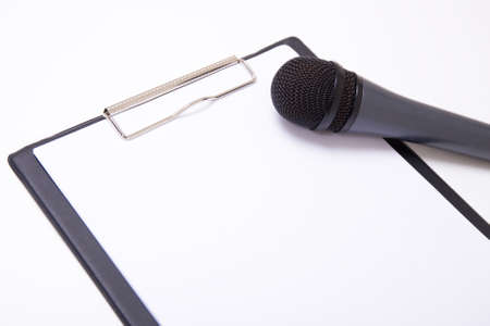 couching: speech or interview concept - microphone and clipboard with blank sheet of paper