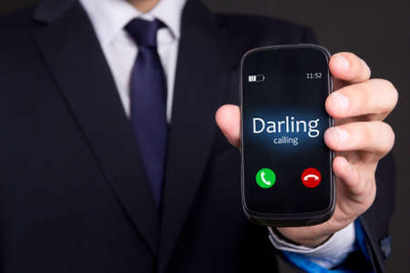 incoming: relationship concept - male hand holding smart phone with incoming call from darling