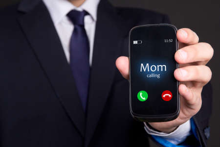 incoming: mom is calling concept - male hand holding smart phone with incoming mother call