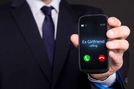 ex: relationship concept - male hand holding smart phone with incoming call from his ex girlfriend