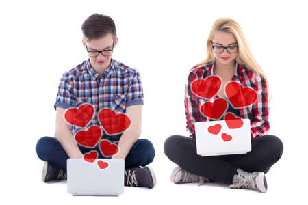 love and friendship: online dating concept - young man and woman sitting with laptops and sending love messages isolated on white background