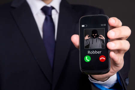 scammer: phone robbery concept - business man hand holding smart phone with incoming call from robber