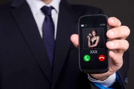 llamando: concepto de la infidelidad - mano masculina que sostiene el teléfono inteligente con llamada entrante de su amante