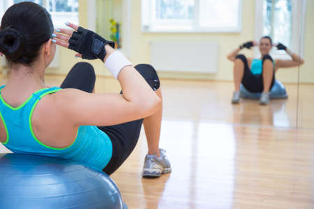 personal training: sport concept - young sporty woman doing exercises on bosu ball in gym