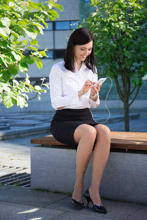 young business woman using smartphone in city park Stock Photo
