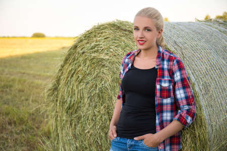 haystacks: young beautiful blonde woman in field with haystacks Stock Photo